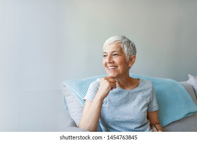 Portrait of beautiful mature woman smiling while sitting at sofa at home. Happy woman relaxing on her couch at home in the sitting room. Shot of a mature woman relaxing at home