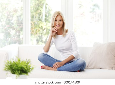 Portrait of beautiful mature woman smiling while sitting at sofa at home.