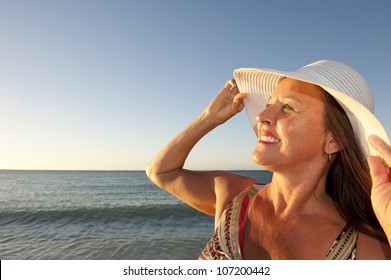 Portrait beautiful mature woman at sunset beach, wearing white wide rimmed hat, friendly and happy, isolated with ocean and blue sky as background and copy space.
