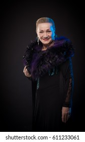 Portrait of a beautiful mature woman in a theatrical costume with boa posing on a black background