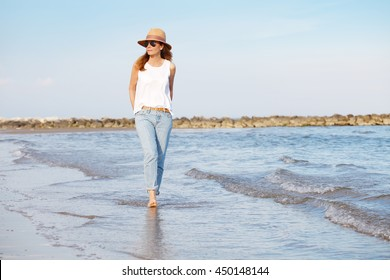 Portrait of a beautiful mature woman walking along a sandy beach while wearing straw hat and sunglasses.