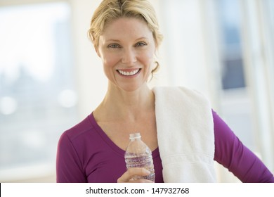 Portrait of beautiful mature woman with water bottle and towel smiling in health club