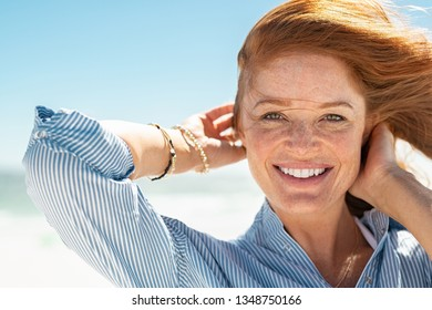 Portrait of beautiful mature woman with wind fluttering hair. Closeup face of healthy young woman with freckles looking at camera. Lady with red hair standing at seaside enjoying breeze at beach.