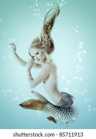 portrait of beautiful mermaid girl with fish tail and long blond hair swimming in ocean magic mythology being original photo compilation