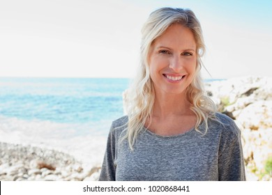 Portrait of beautiful middle age healthy woman visiting beach on sunny holiday vacation trip, looking smiling, outdoors. Mature female joyful expression, active recreation leisure lifestyle, exterior.