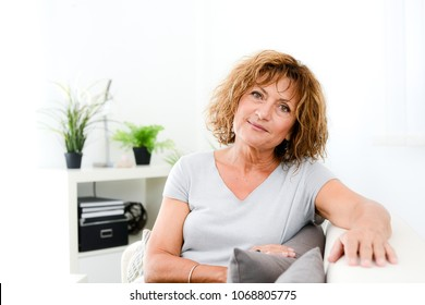 portrait of beautiful middle age mature senior woman posing on a sofa at home
