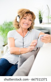 portrait of beautiful middle age mature senior woman listening to music with smart-phone on sofa at home