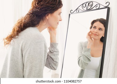 Portrait of beautiful middle age woman looking into mirror in bathroom applying cream on face, healthy skin care cosmetics. Mature female reflection, fresh clean stylish in robe, wellness lifestyle.