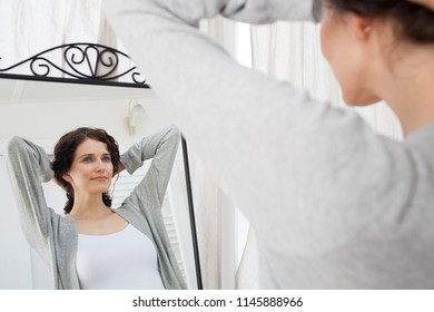 Portrait of beautiful middle age woman looking into mirror in bathroom holding hair up, healthy grooming skin care cosmetics. Mature female reflection, fresh clean stylish in robe, wellness lifestyle.