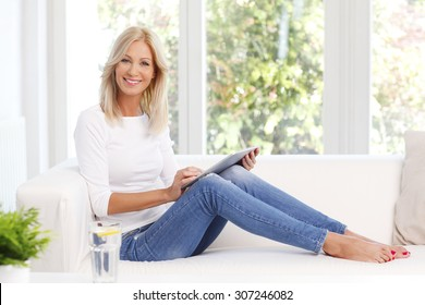 Portrait of beautiful middle age woman using digital tablet while sitting at home at sofa.