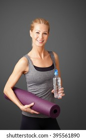 Portrait of a beautiful middle age woman standing at isolated background while holding in her hands a yoga mat and a bottle of water.