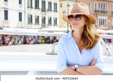 Portrait of beautiful middle aged casual woman enjoying boat tour in Venice. Smiling female wearing a straw hat and sunglasses while relaxing on holiday.