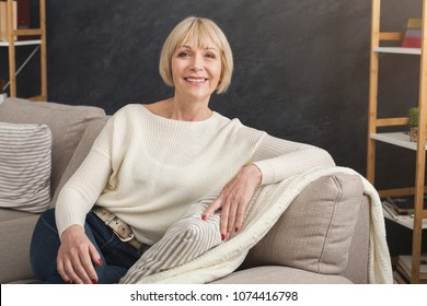 Portrait of beautiful middle aged woman sitting on sofa. Attractive female relaxing at home after hard day.
