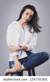 Portrait of beautiful middle aged woman wearing white shirt and jeans in photo studio