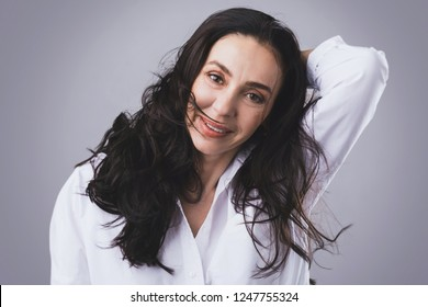 Portrait of beautiful middle aged woman wearing white shirt  in photo studio