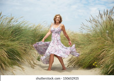 Portrait of a beautiful middle aged woman dancing in the sand at the beach