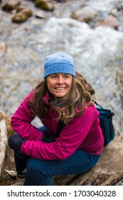 A portrait of a beautiful middle aged woman taking a break near Gore Creek in Vail, Colorado, USA