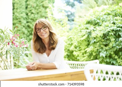 Portrait of a beautiful middle aged woman giving you a smile while she is relaxing outdoor.