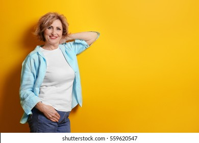 Portrait of beautiful middle-aged woman on yellow background