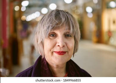 Portrait of beautiful middle-aged woman with short hair who walks inside shopping center.