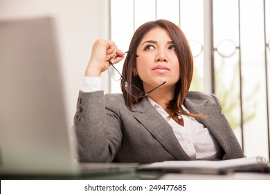 Portrait of a beautiful mixed-race business woman looking up and daydreaming at her office