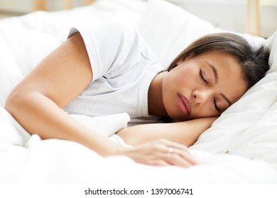 Portrait of beautiful Mixed-Race woman sleeping serenely on white pillows, copy space