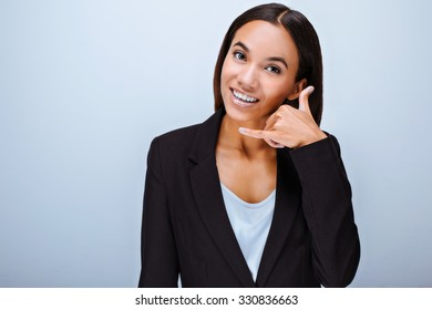 Portrait of beautiful mixed-race young woman standing on grey background. Business woman wearing suit. Smiling woman looking at camera and making call me gesture