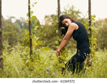 Portrait of beautiful model in black on nature background, posing.