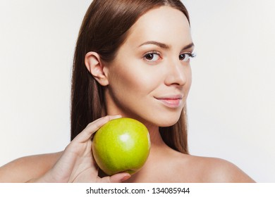 portrait of beautiful model with clean fresh skin. holding green apple
