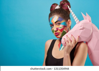 Portrait of beautiful model posing, looking at camera. Charming woman holding hand on 3D paper unicorn head. Funky girl has pop art creative make up. Papercraft concept.