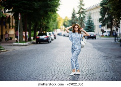 Portrait of a beautiful model in striped overall posing with hat and a backpack on a street with trees in a town.