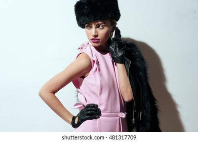 Portrait of beautiful model wearing pink dress, black fur coat, leather gloves and cap in a studio. White background.