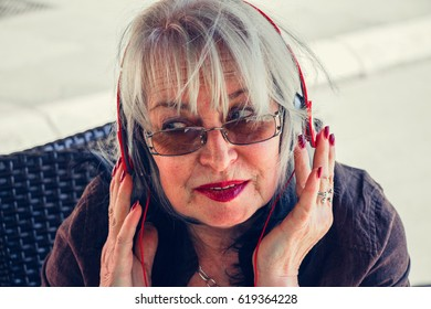 Portrait of beautiful modern senior   woman with red lipstick enjoys a sunny day and listening to music on the headset.