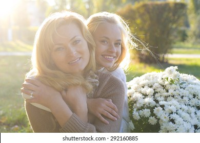 portrait of a beautiful mother and daughter in the park in autumn