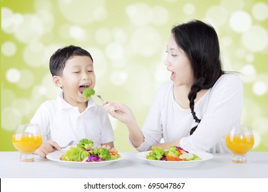 Portrait of beautiful mother feeding her son with fresh salad. Shot with bokeh background