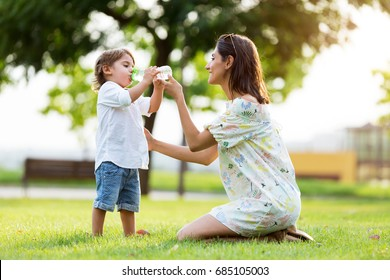 Portrait of beautiful mother gives child a drink of water in the park.