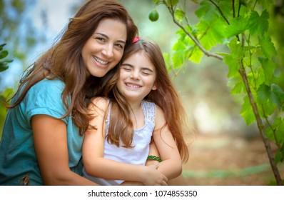 Portrait of a beautiful mother with her cute little daughter with pleasure spending time together in fresh green garden, happy family life