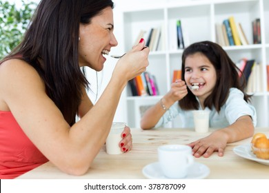 Portrait of beautiful mother and her daughter eating iogurt at home.