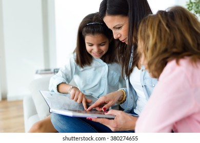 Portrait of beautiful mother with her daughters reading a book at home.