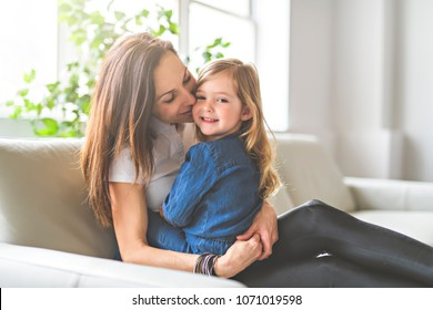 Portrait of a beautiful mother and her little girl sitting at home