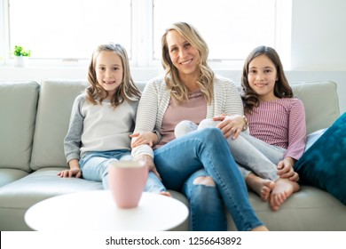 A Portrait of a beautiful mother and her little girls sitting at home and sharing a happy moment together.