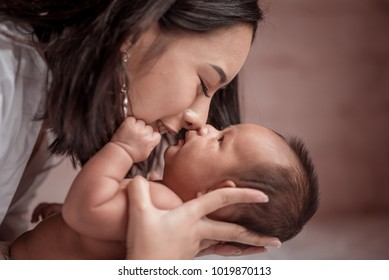 Portrait beautiful mother kiss her baby child. Mom nursing baby. mom and baby boy relax at home. Nursery interior. Mother breast feeding baby. Family at home. Mom's love. selected focus, vintage style