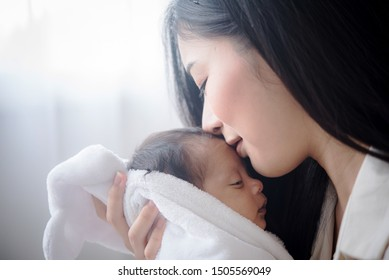 Portrait beautiful mother kiss her baby child. Mom nursing baby. mom and baby boy relax at home. Nursery interior. Mother breast feeding baby. Family at home. Mom's love. selected focus