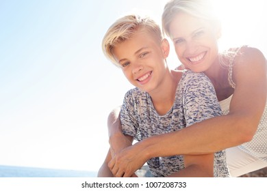 Portrait of beautiful mother and son hugging with joy and love, outdoors. Happy expressions, family closeness. Loving care, recreation lifestyle in sunny exterior with sun flare. Positive relations.