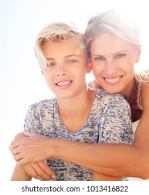 Portrait of beautiful mother and son hugging with love, outdoors. Smiling happy expressions, family closeness. Loving care, recreation lifestyle in sunny exterior with sun flare. Positive relations.