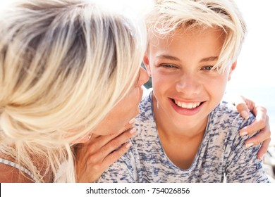 Portrait of beautiful mother and son hugging talking with joy and love, outdoors. Happy expressions, family closeness pride. Loving care, recreation lifestyle in sunny exterior. Positive relations.