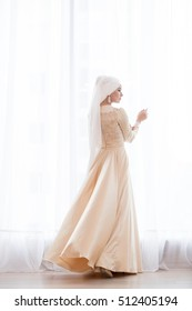 Portrait of a beautiful muslim bride in gold wedding dress with Beautiful white headdress standing near a window, back view