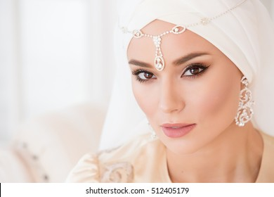 Portrait of a beautiful muslim bride with make up in pink wedding dress with Beautiful white headdress close up