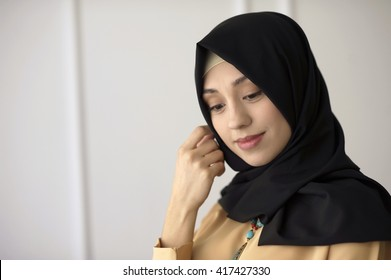 portrait of a beautiful Muslim girl in a black scarf on his head on a light classical background