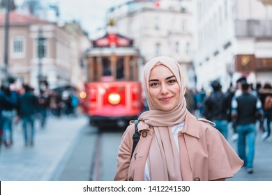 Portrait of beautiful Muslim woman in headscarf and fashionable modern clothes stands at Istiklal street,Istanbul,Turkey.Modern Muslim women lifestyle or travel tourist concept